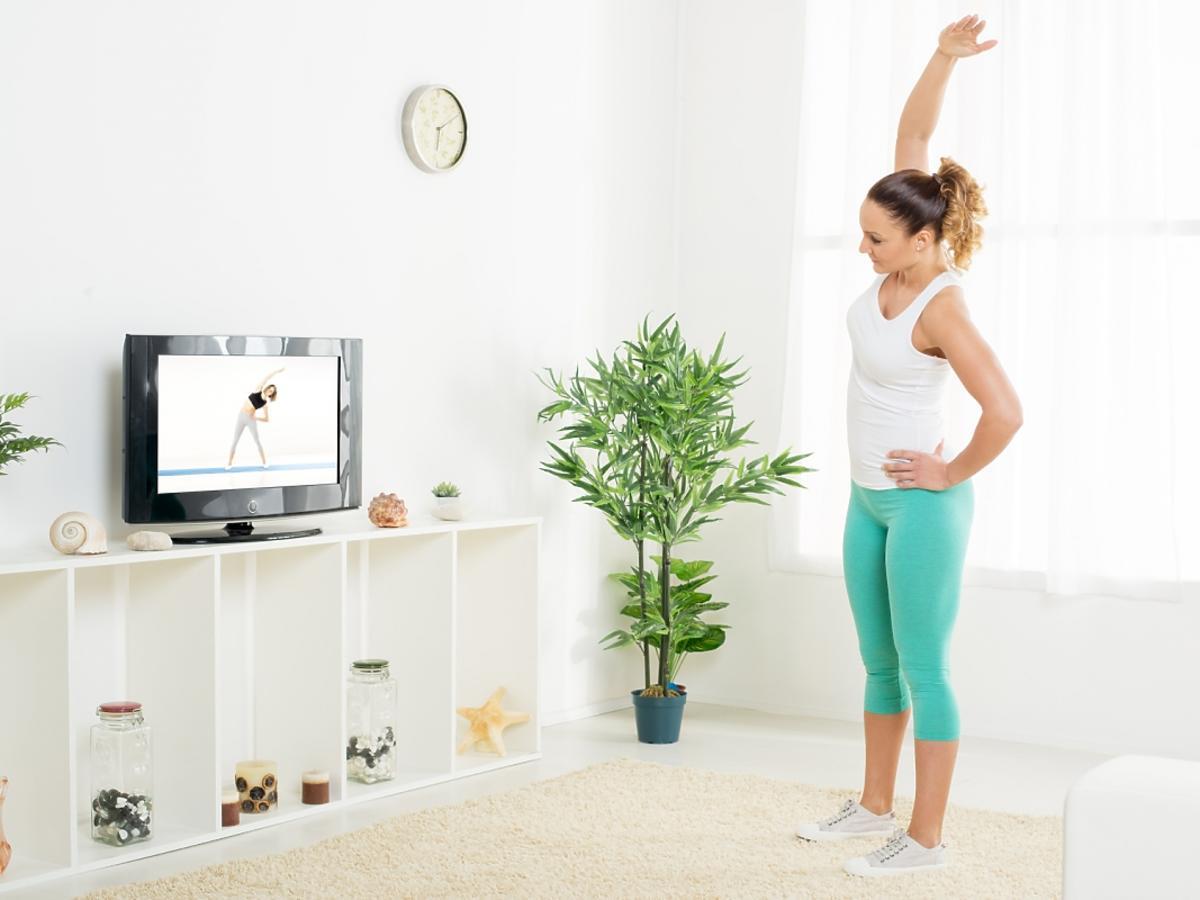kobieta ćwiczy w domu przed telewizorem