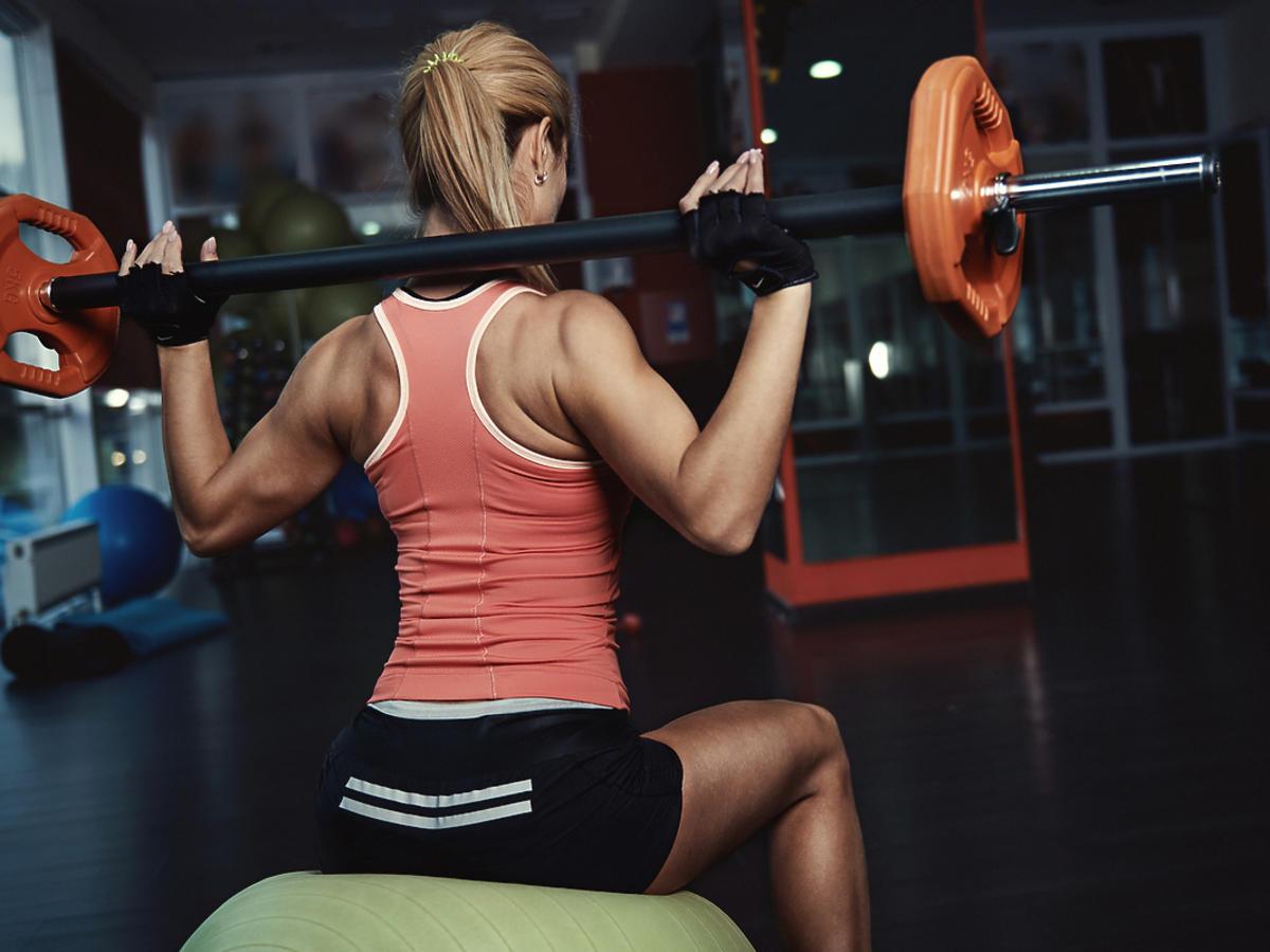 Kobieta ćwiczy ze sztangą