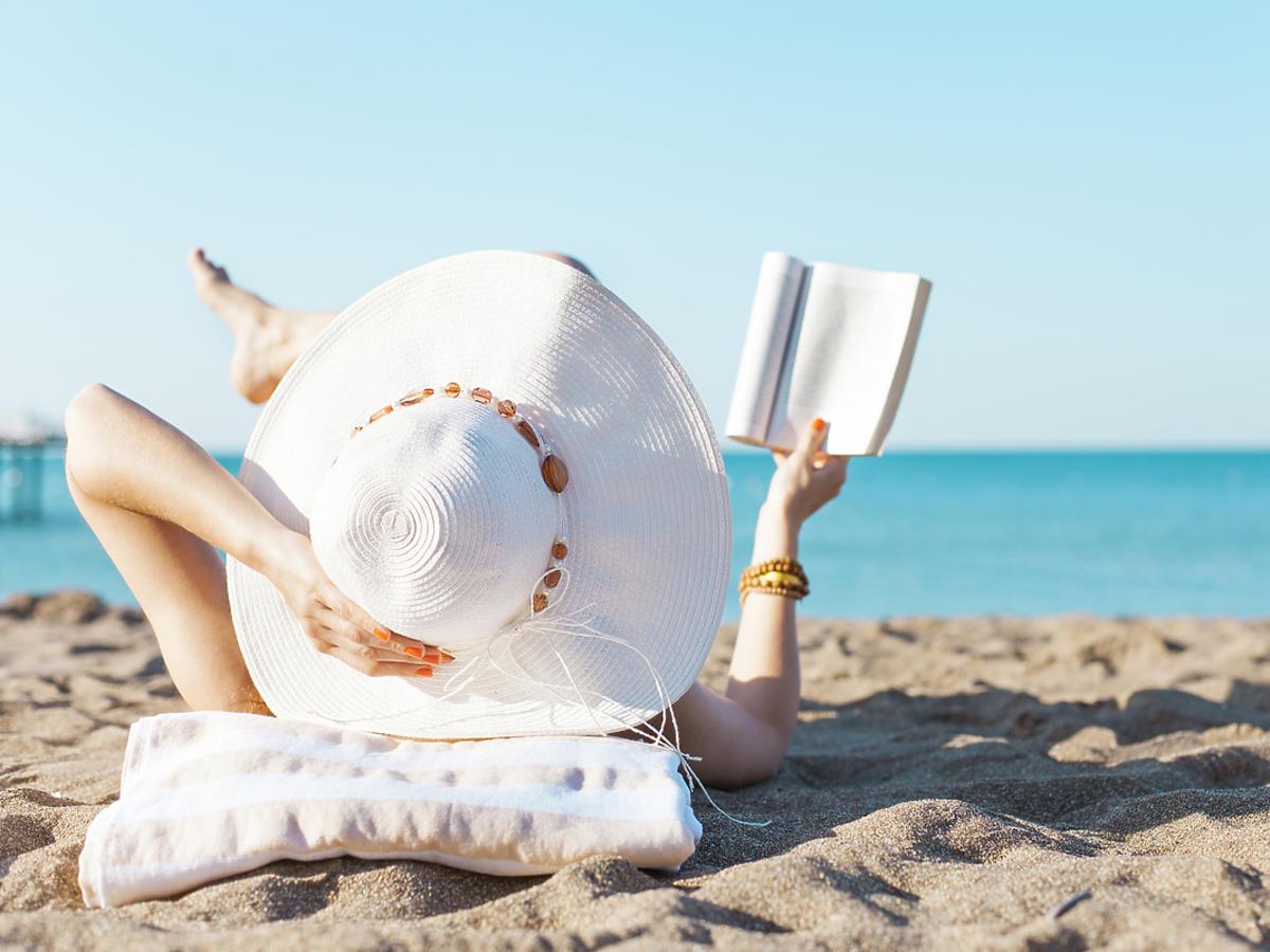 Kobieta czyta na plaży książkę leżąc na leżaku.