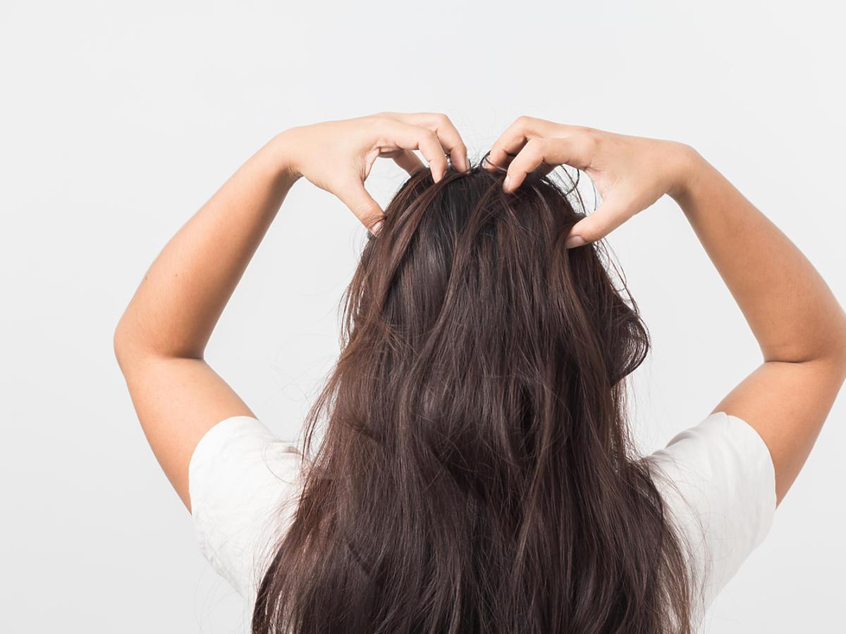 kobieta drapiąca się po włosach