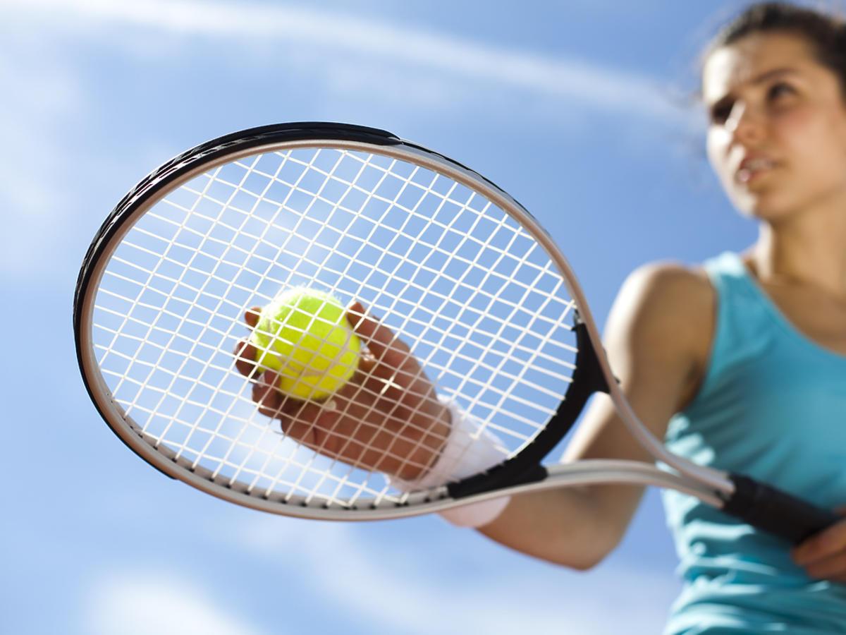Kobieta gra w tenis ziemny.