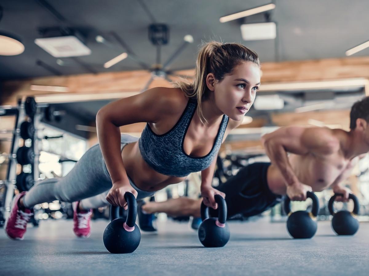 Kobieta i mężczyzna ćwiczą na siłowni.