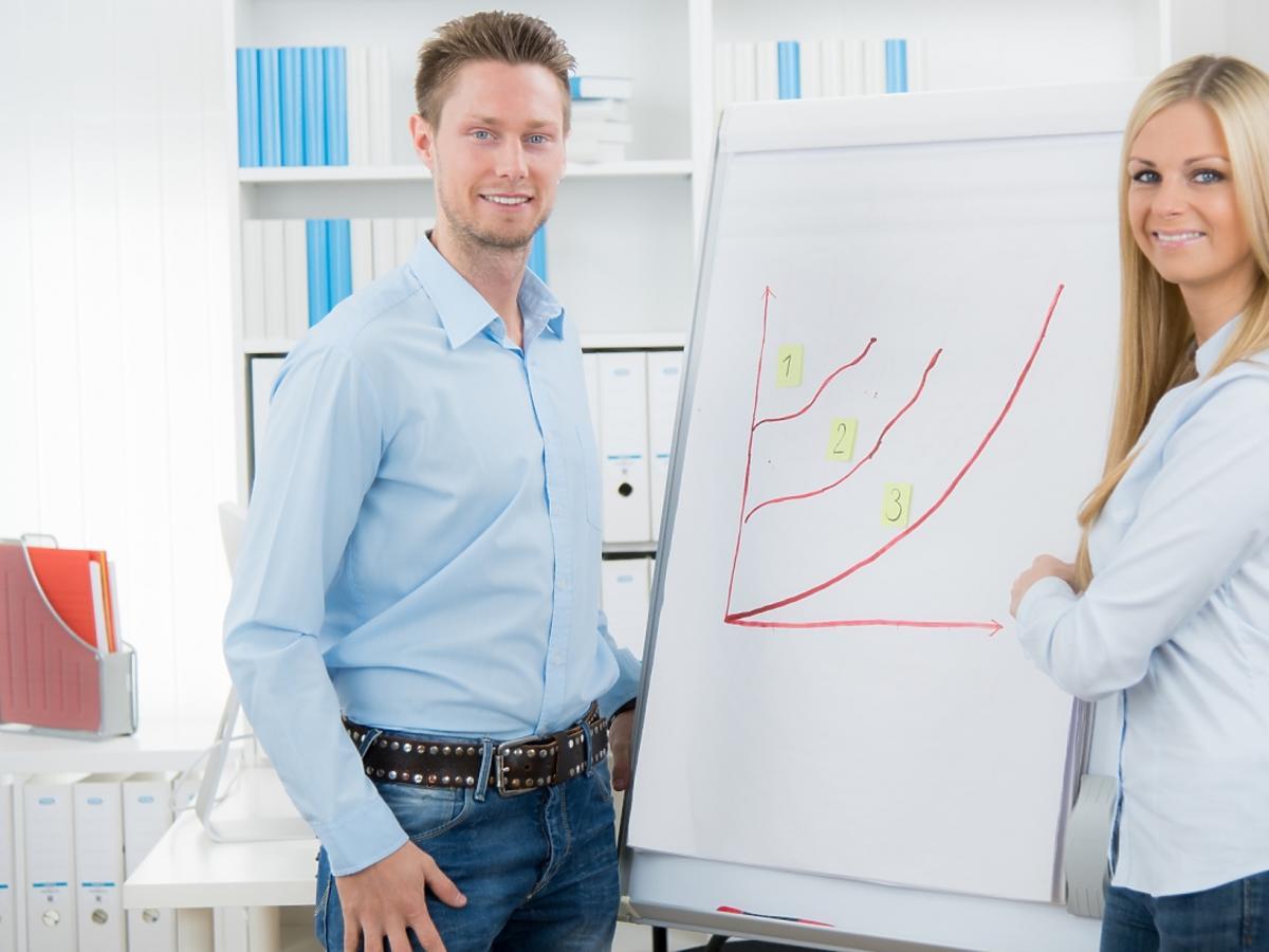 kobieta i mężczyzna stoją przy tablicy