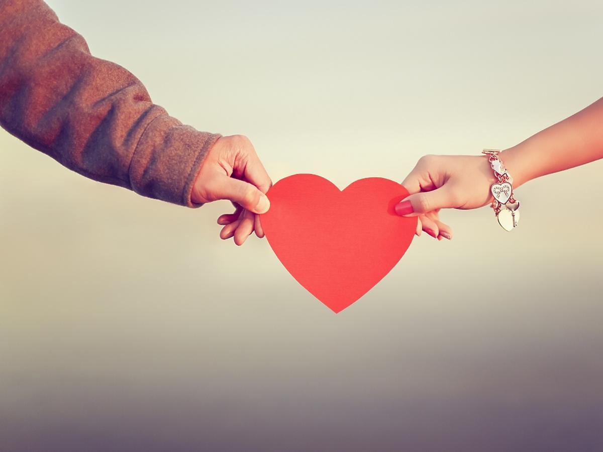Kobieta i mężczyzna trzymają w dłoniach papierowe serce.