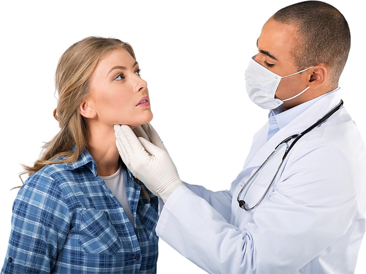 kobieta jest badana przez lekarza w masce i rękawiczkach
