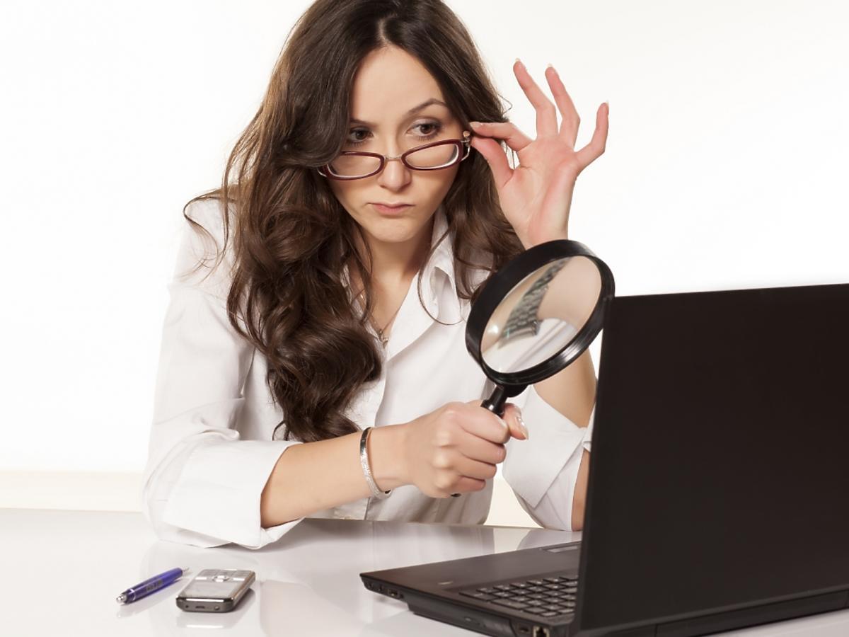 Kobieta, która podejrzliwie patrzy na monitor komputera