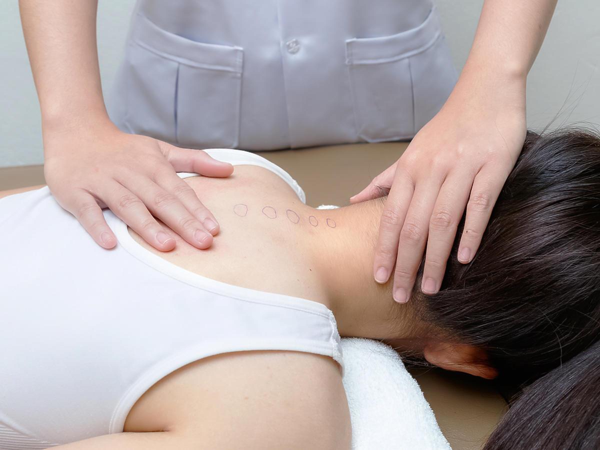 kobieta leżąca na kozetce rehabilitant trzyma ręce na jej karku i plecach