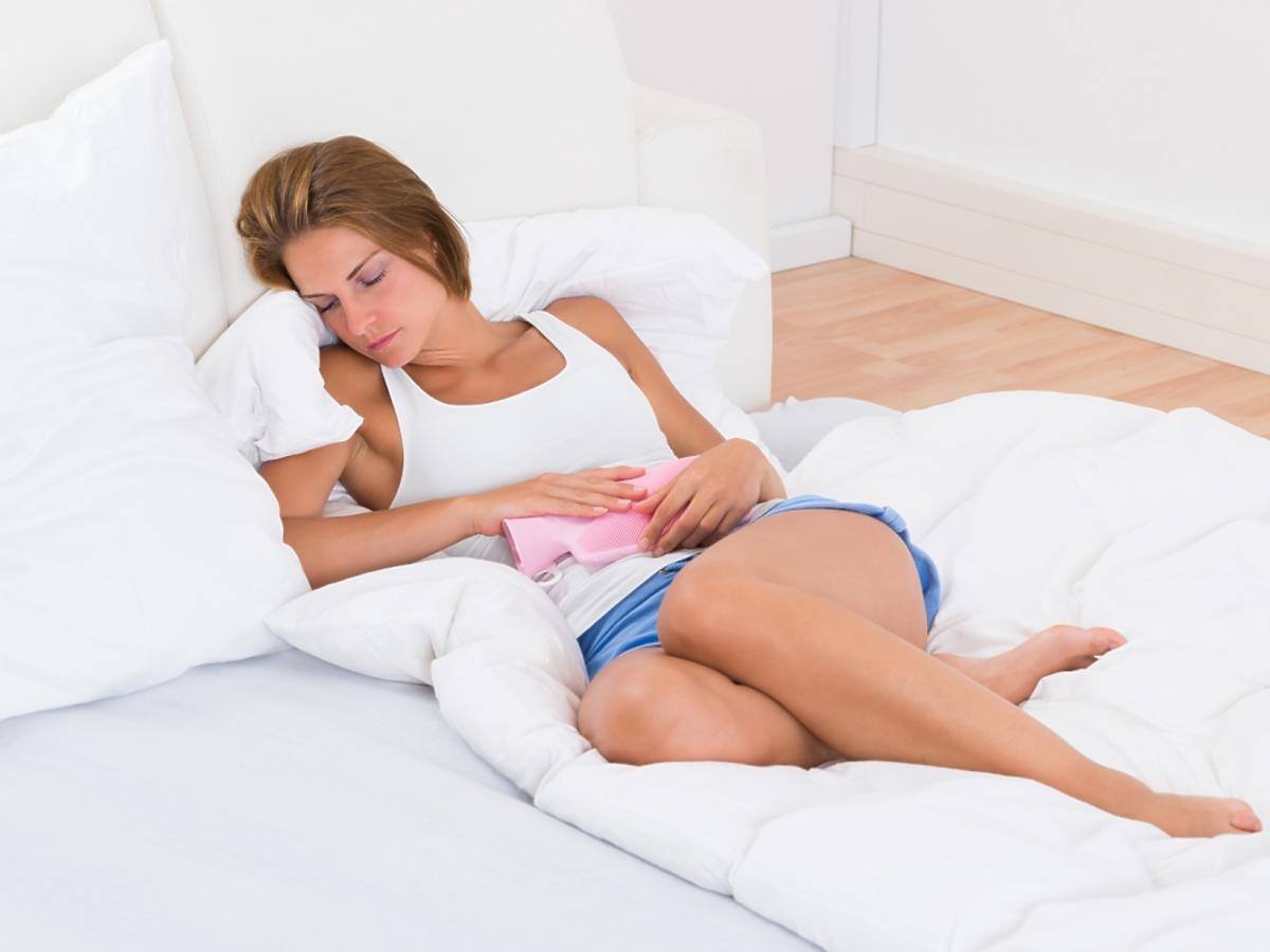 Kobieta leżąca na łóżku, trzymająca się za brzuch.