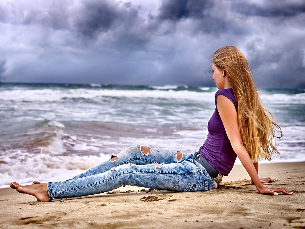 Kobieta leżąca na plaży w podartych jeansach