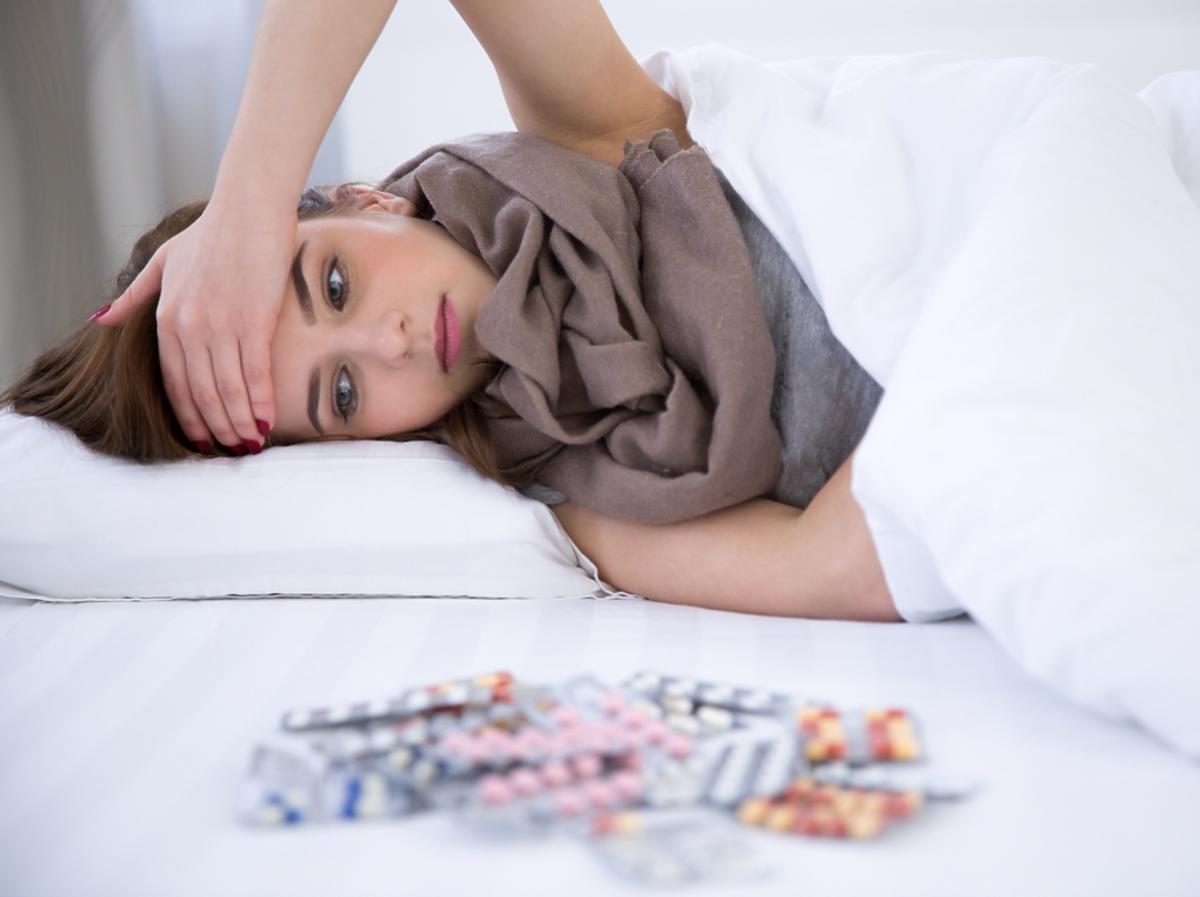 kobieta leżaca w łóżku i tabletki