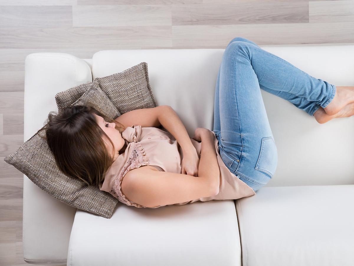 Kobieta leży na kanapie i trzyma się za brzuch.