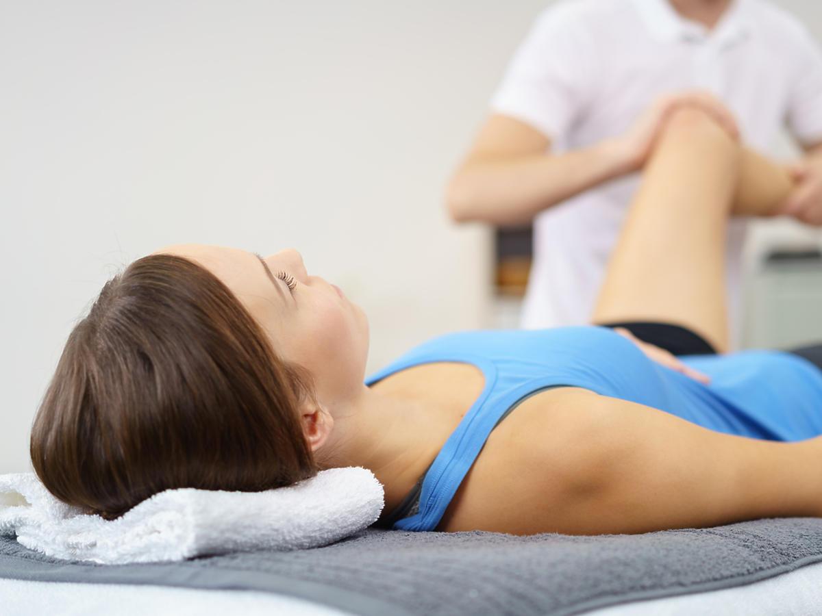 Kobieta leży na łóżku, fizjoterapeuta przeprowadza terapię.