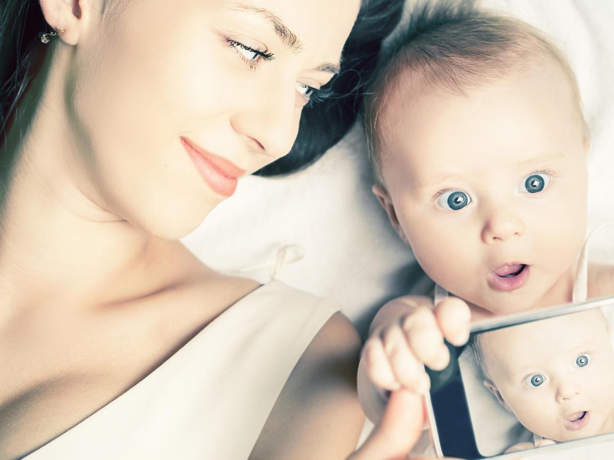 Kobieta leży na łóżku z dzieckiem, które trzyma w dłoniach telefon komórkowy