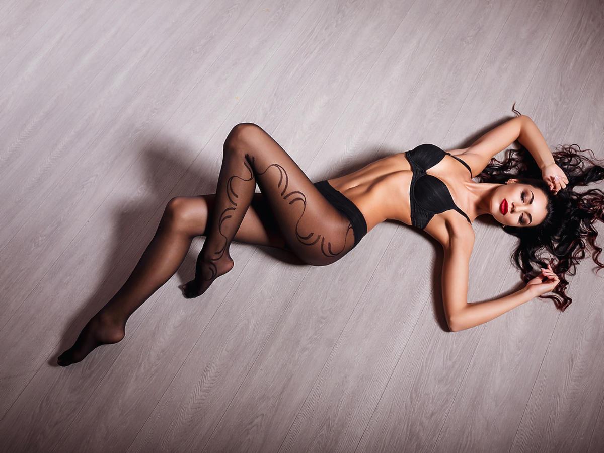 Kobieta leży na ziemi w eleganckiej bieliźnie i rajstopach.