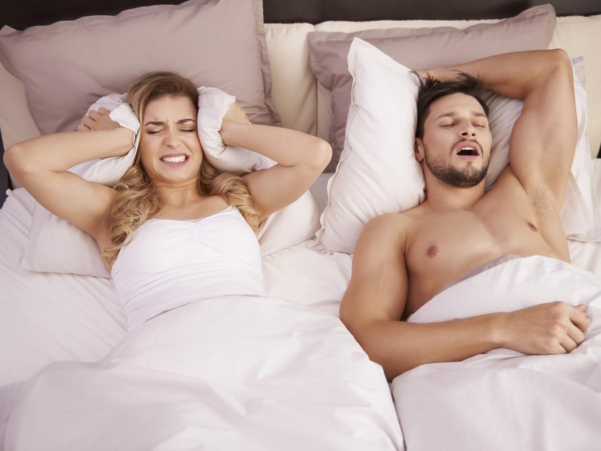 kobieta leży w łóżku z chrapiącym mężczyzną