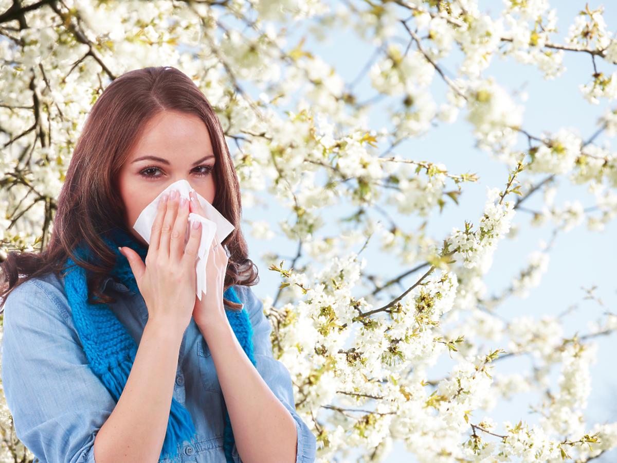 Kobieta ma alergię i wyciera nos.