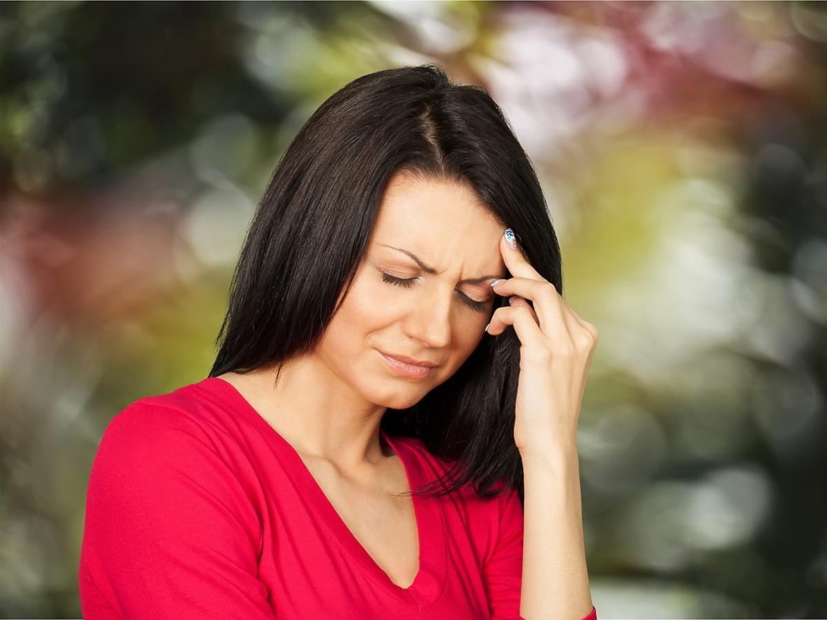Kobieta ma zawroty głowy, trzyma się za głowę z zamkniętymi oczami