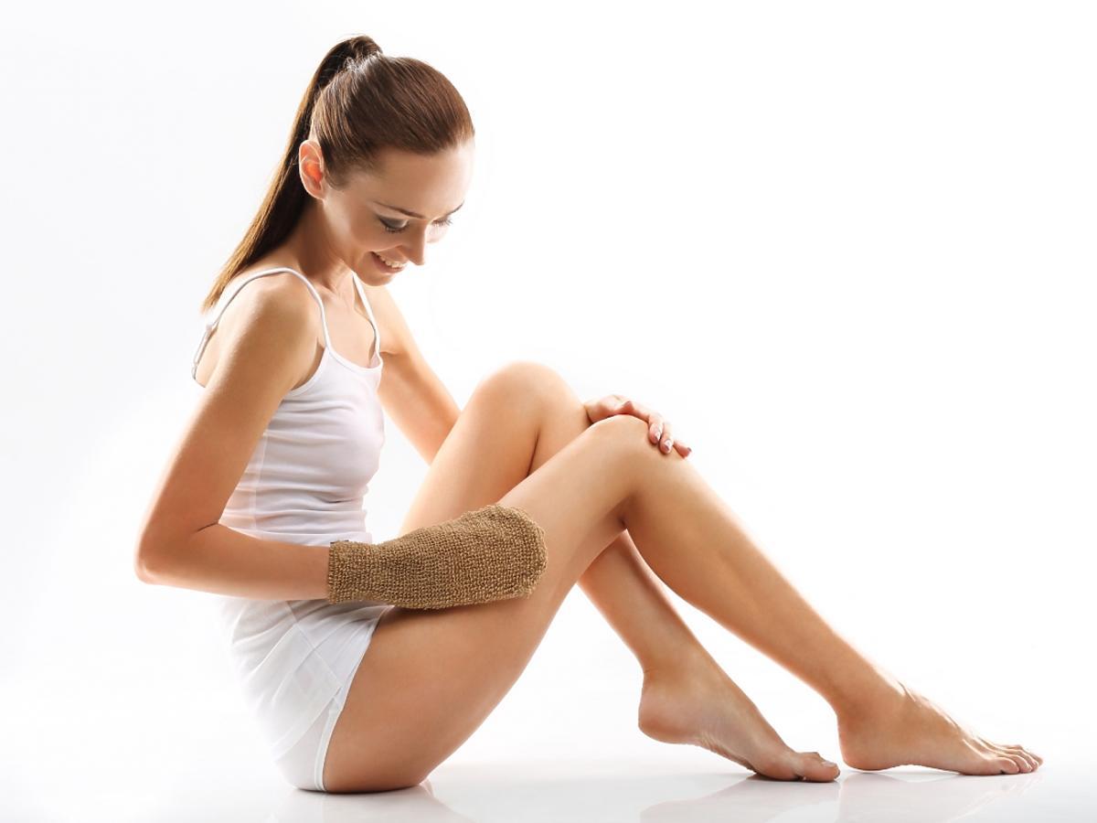 Kobieta masuje nogi rękawicą do masażu