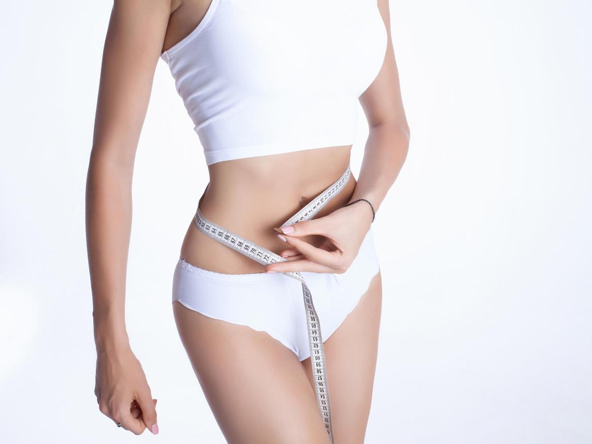 Kobieta mierzy obwód talii centymetrem.