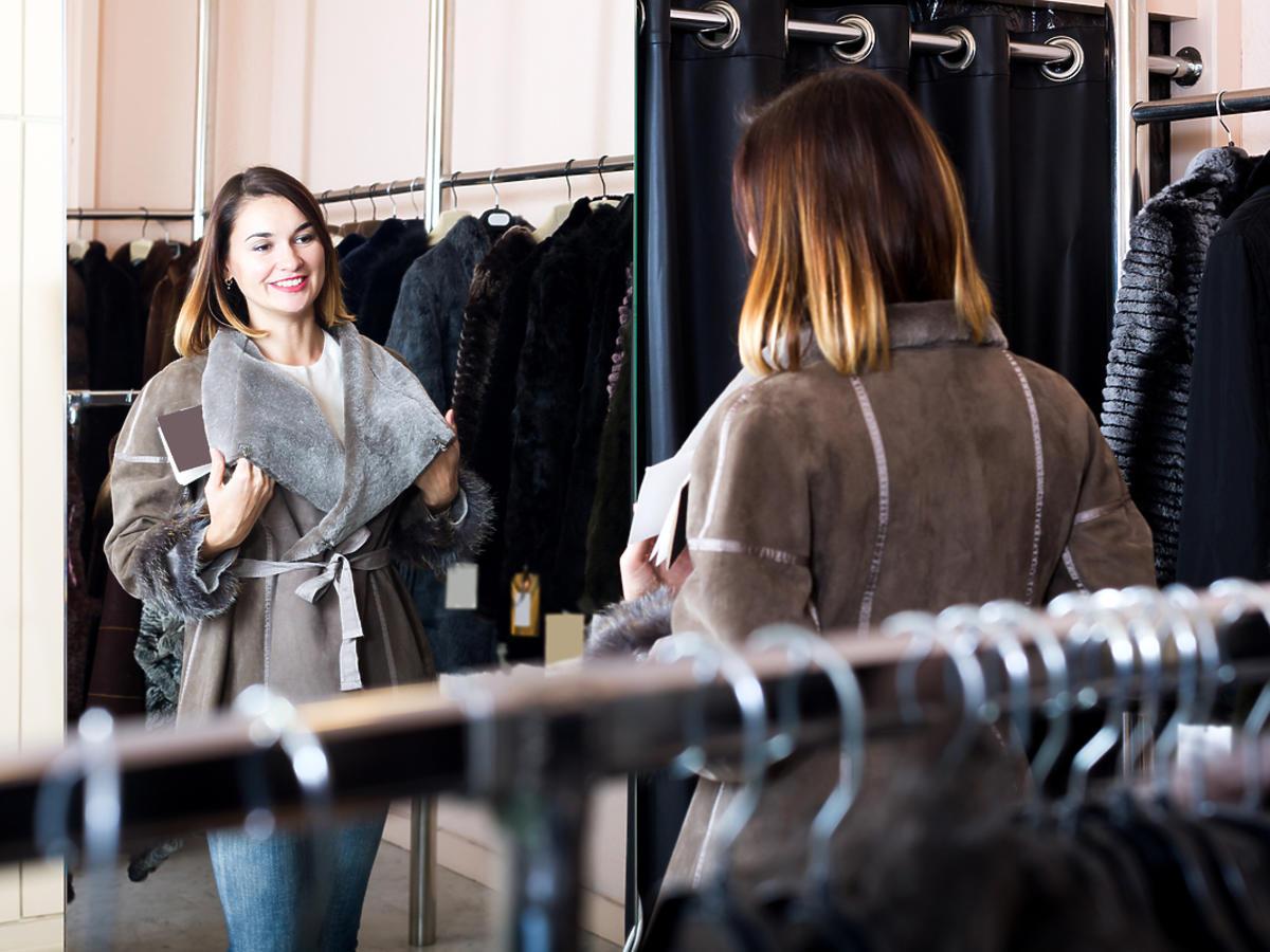 kobieta mierzy w sklepie odzieżowym płaszcz