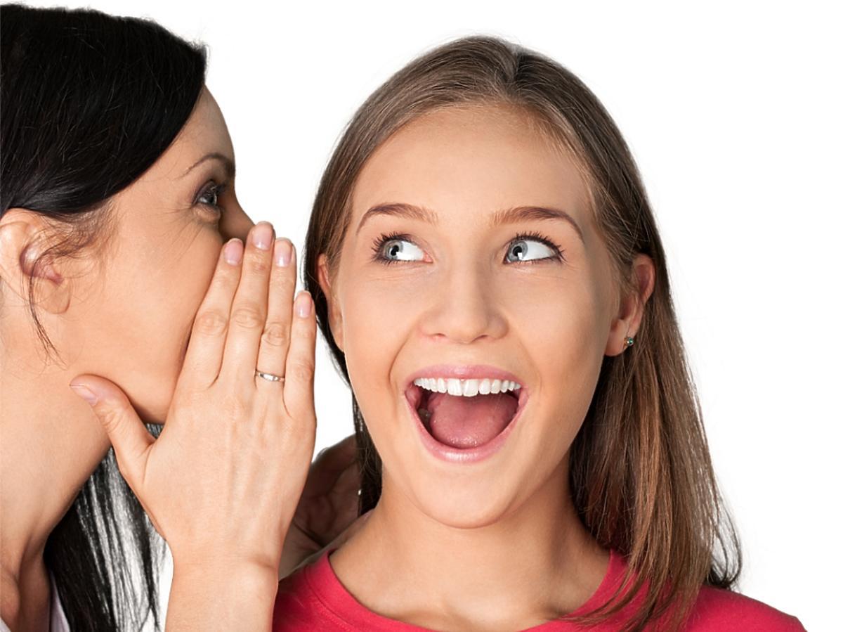 kobieta mówi coś drugiej na ucho