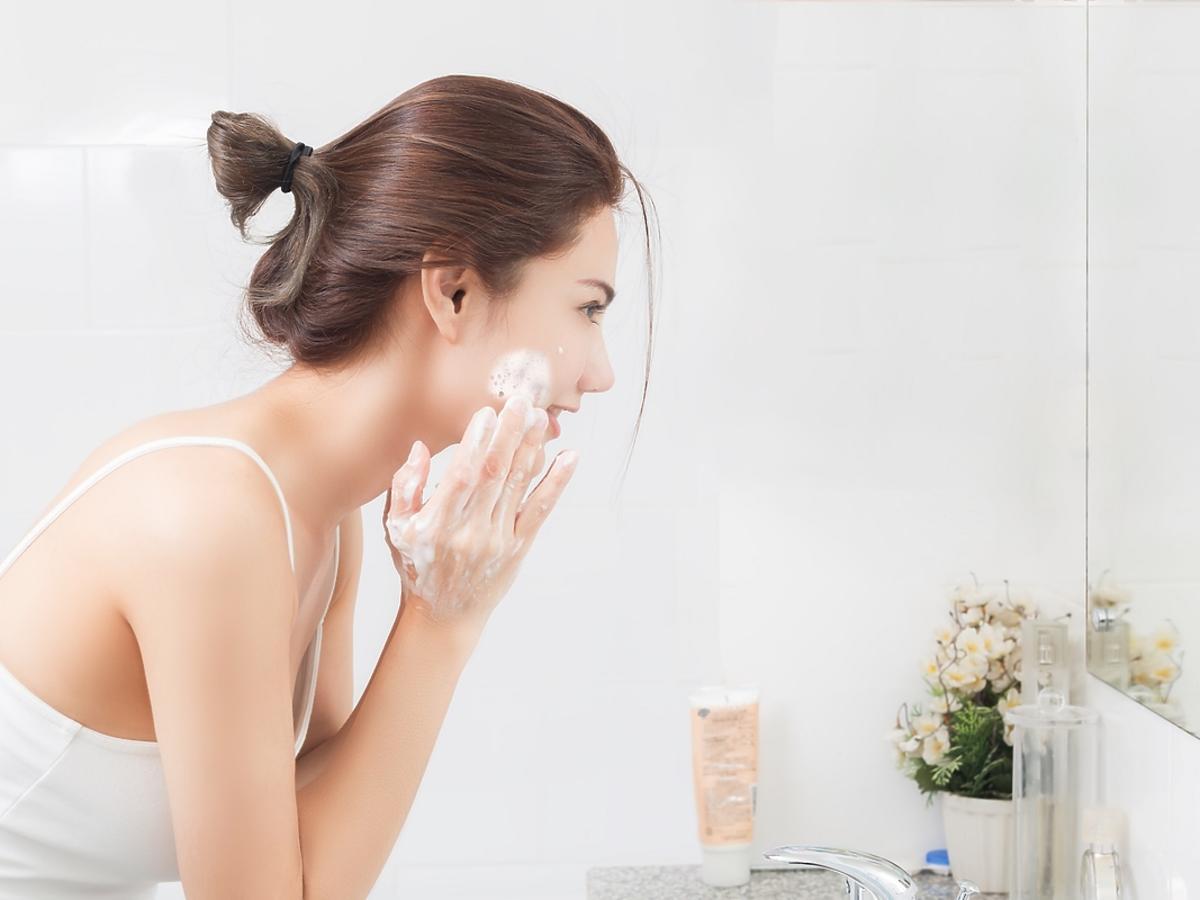 Kobieta myje twarz pudrem myjącym.