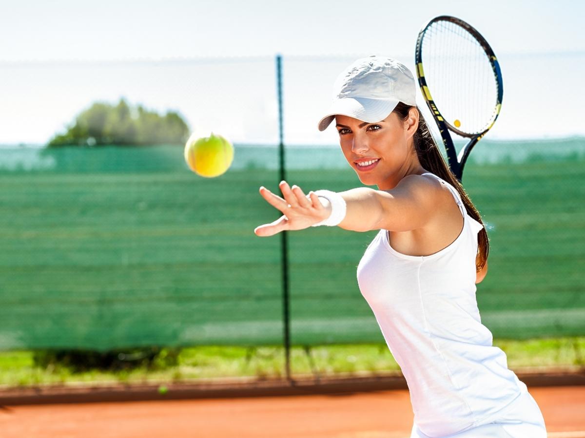 kobieta na korcie tenisowym trzymająca rakietę do tenisa w ręku