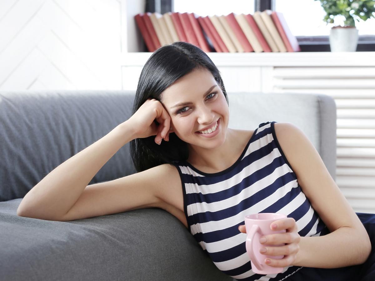 kobieta na łóżku pije kawę