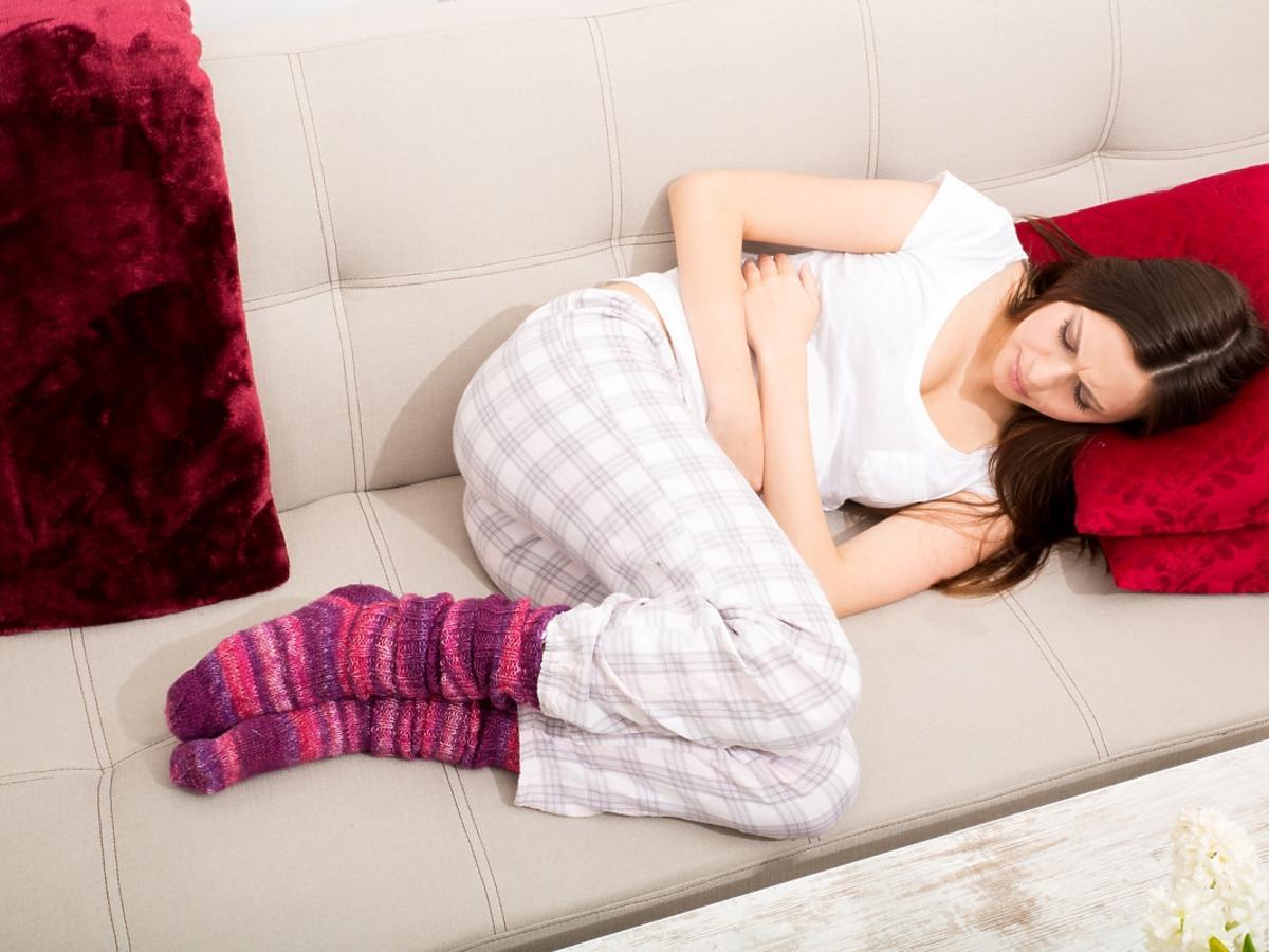 Kobieta na łóżku z bólem brzucha