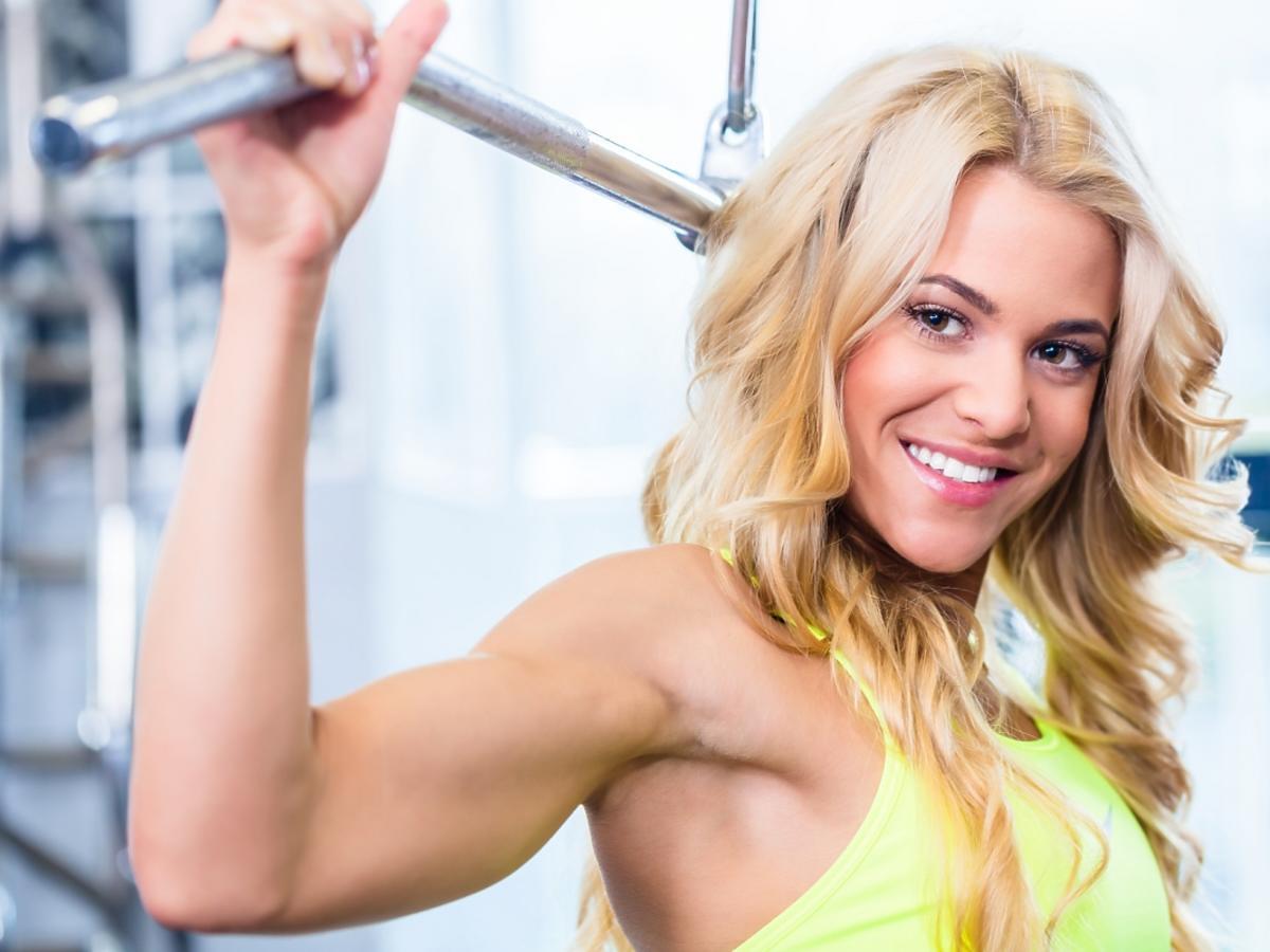 Kobieta na siłowni ćwiczy na maszynie