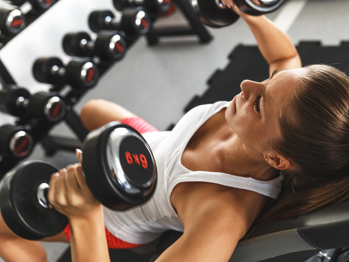Kobieta na siłowni podnosi sztangielkę.