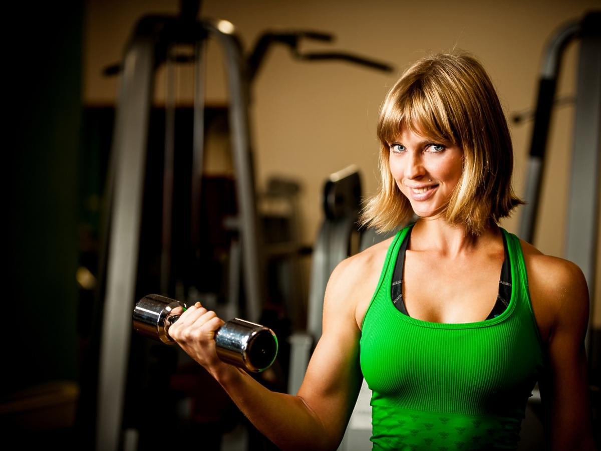 Kobieta na siłowni z hantlami w dłoniach