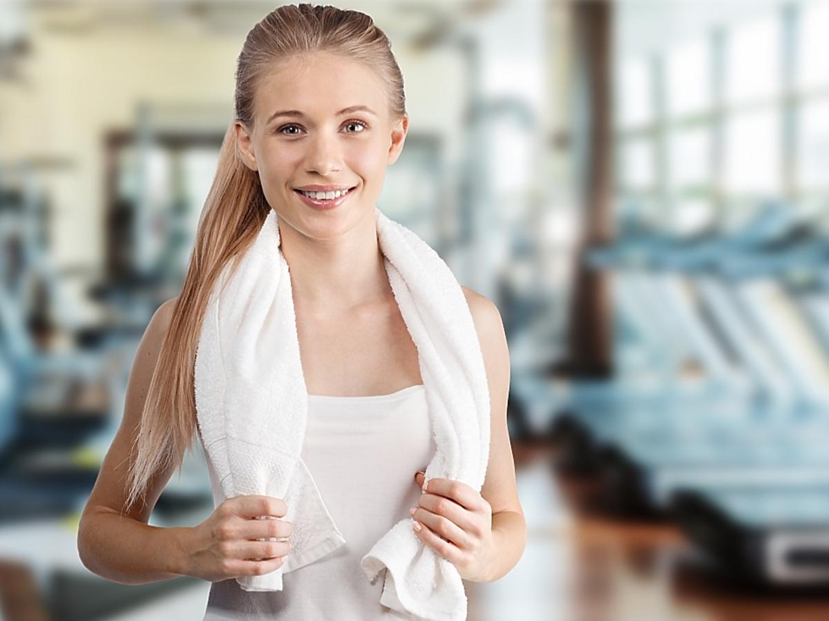 kobieta na siłowni z ręcznikiem