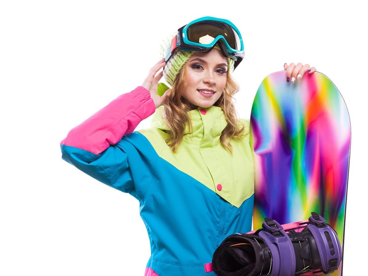 Kobieta na stoku z deską snowboardową.
