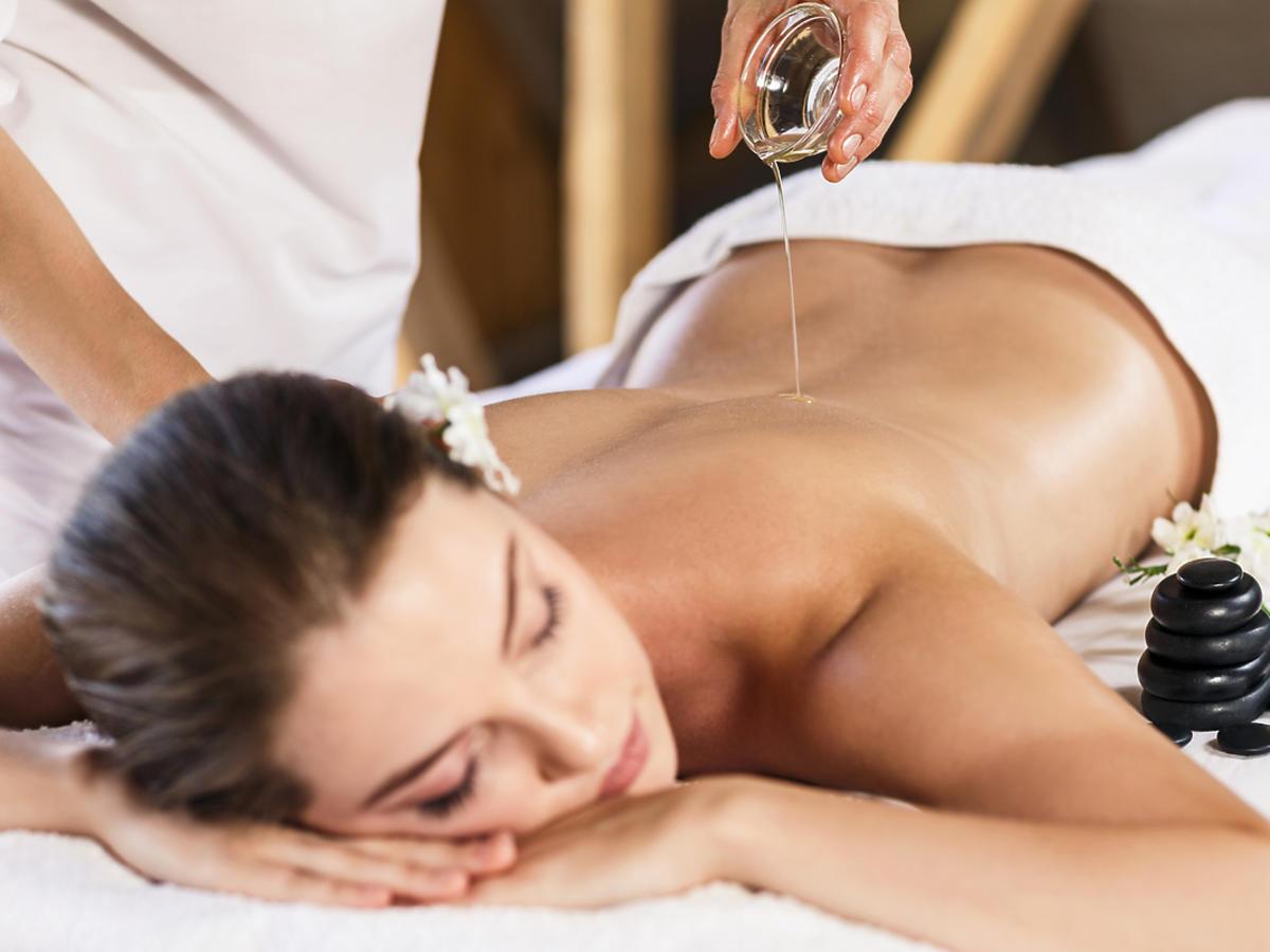 kobieta na stole do masażu ma wylewany olej na plecu