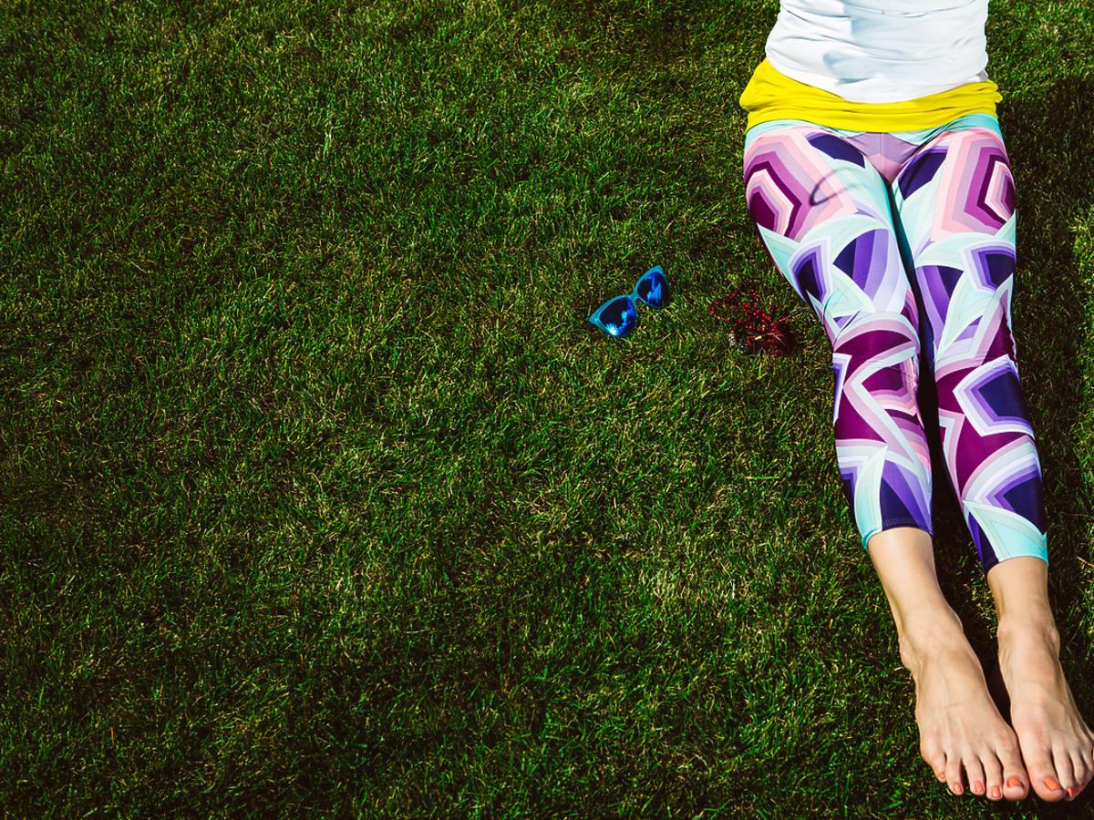 kobieta na trawie w kolorowych legginsach