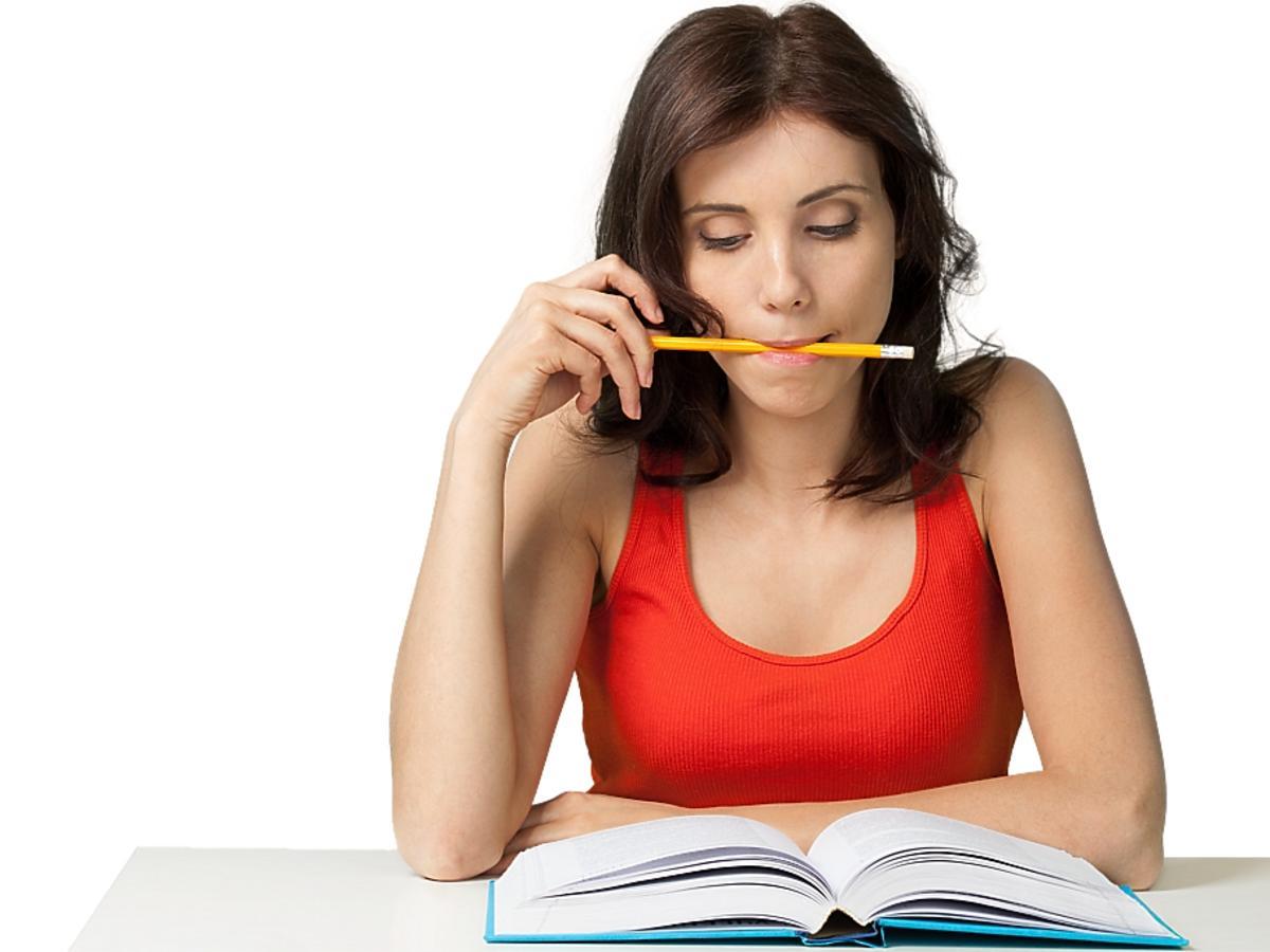 kobieta nad książką z ołówkiem w ustach