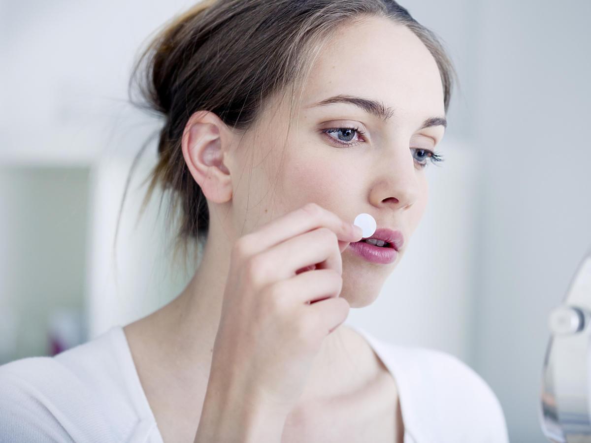 kobieta nakładająca przed lustrem plaster na opryszczkę