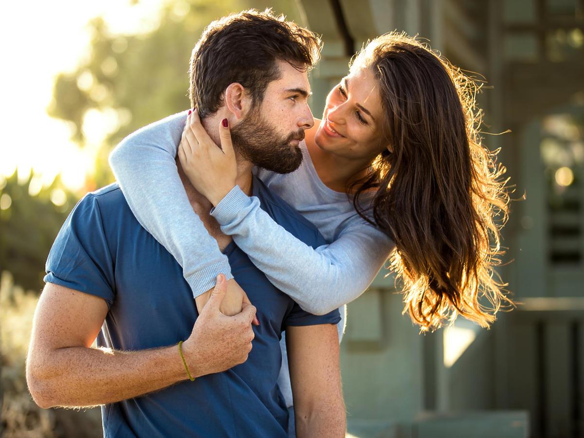 Kobieta obejmuje mężczyznę i uśmiecha się do niego