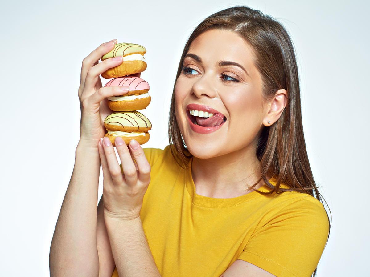 Kobieta oblizująca się na widok trzymanych słodkości