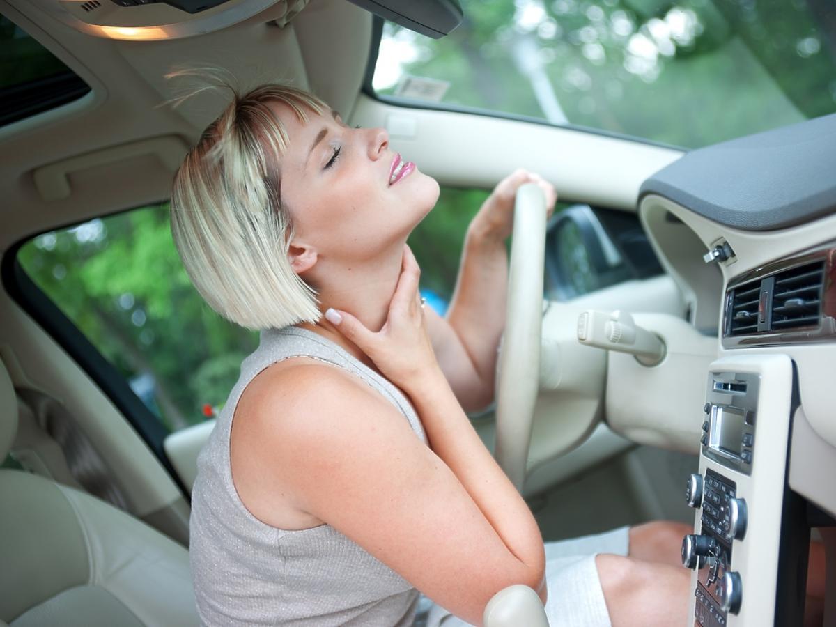 Kobieta ochładza się klimatyzacją w samochodzie.