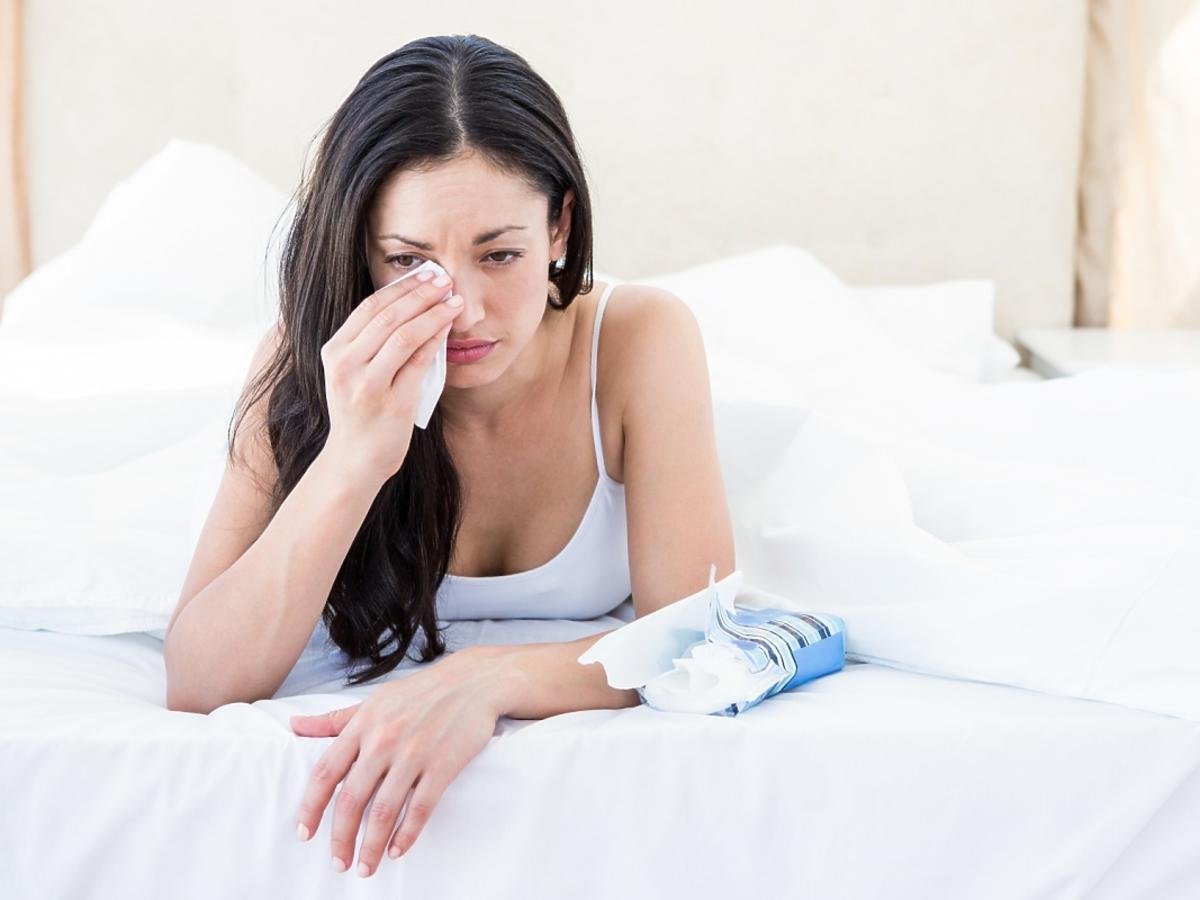 kobieta ociera łzy leżąc na łóżku