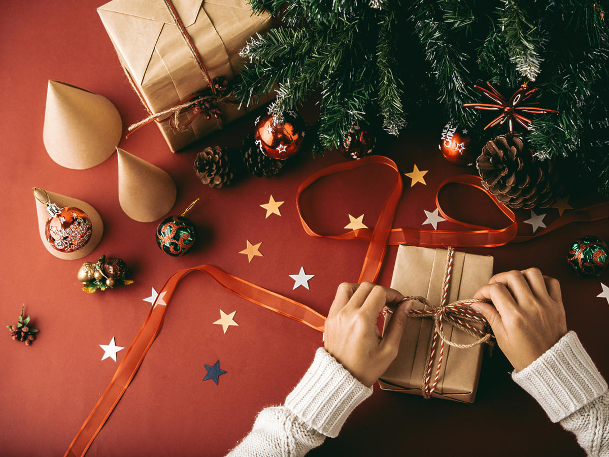 Kobieta pakuje świąteczny prezent dla bliskiej osoby.