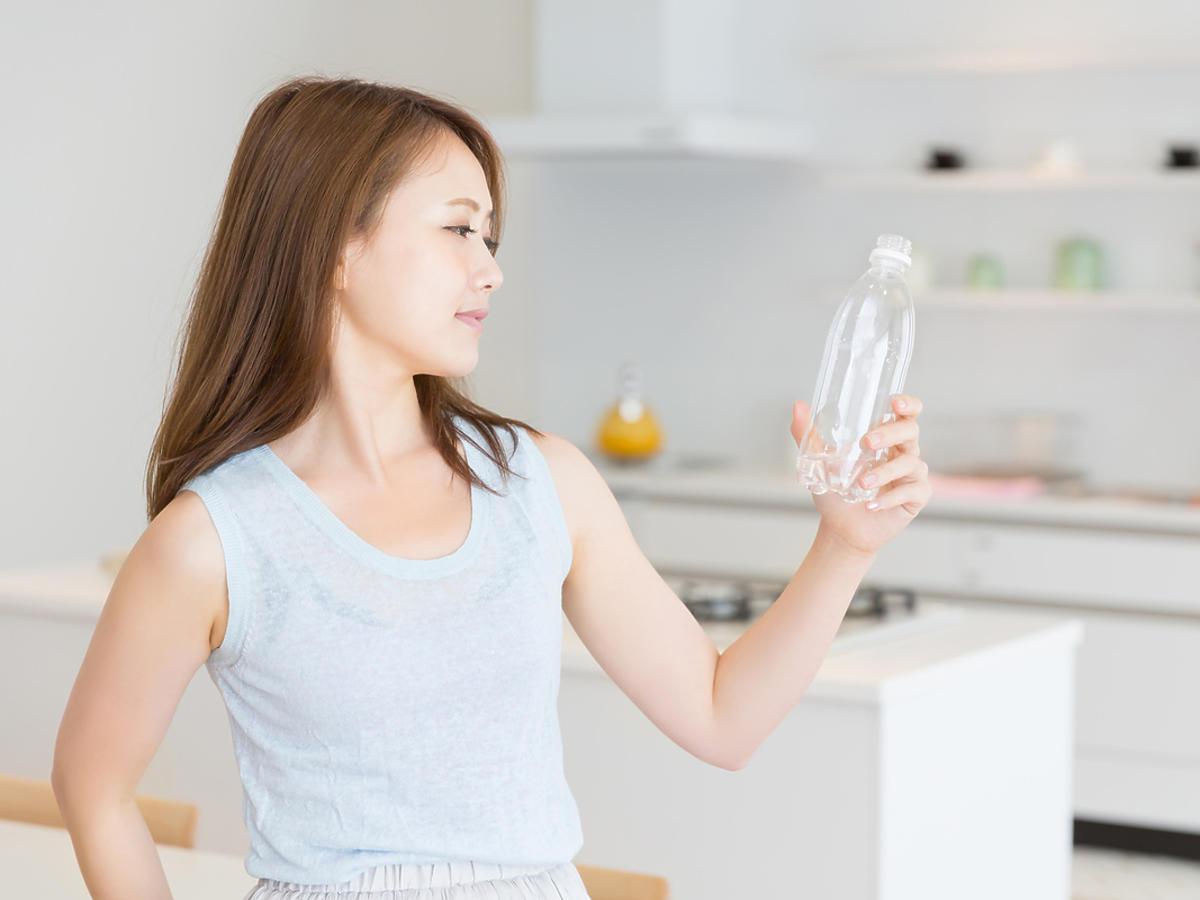 kobieta patrzy na butelkę z wodą