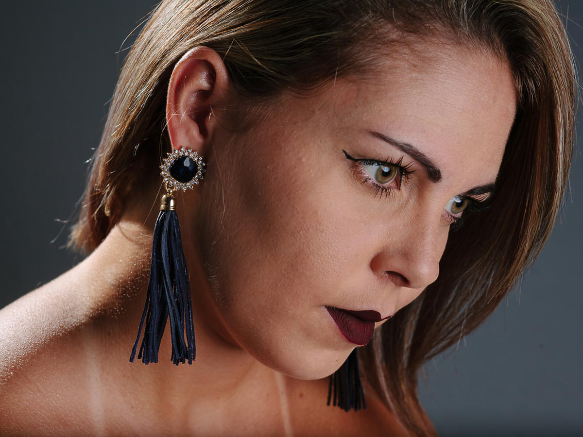 Kobieta patrzy w bok, w uszach ma długie kolczyki.