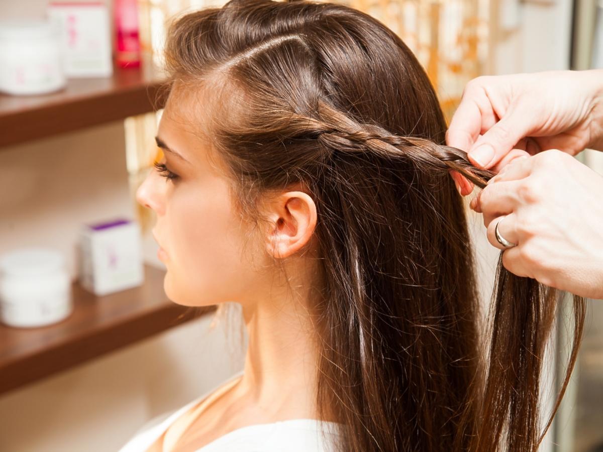 Kobieta plecie warkocz, część długich włosów zostawia rozpuszczonych