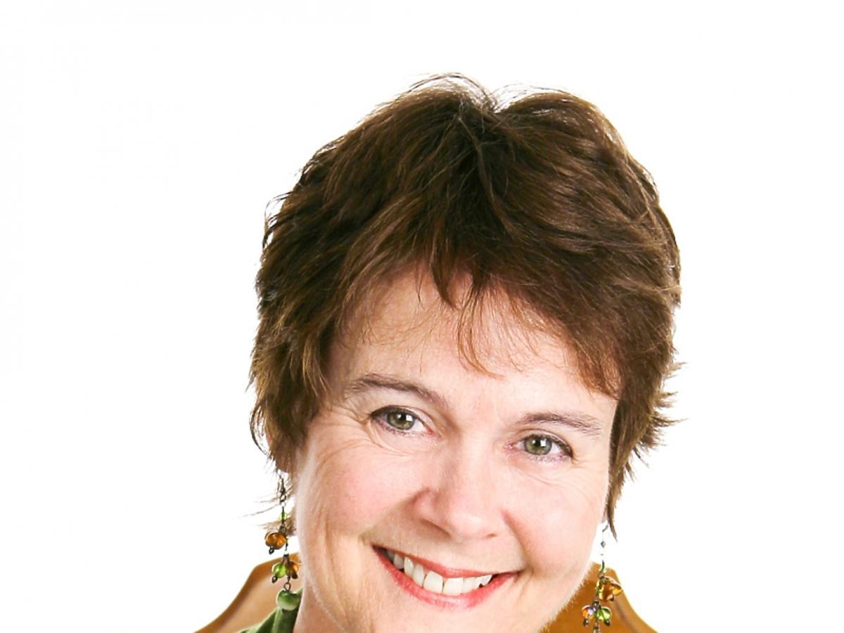 Kobieta po 50. w krótkich włosach i zielonym sweterku