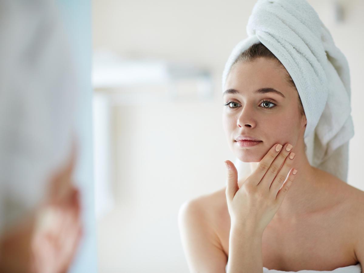 Kobieta po kąpieli ogląda swoją twarz w lustrze.