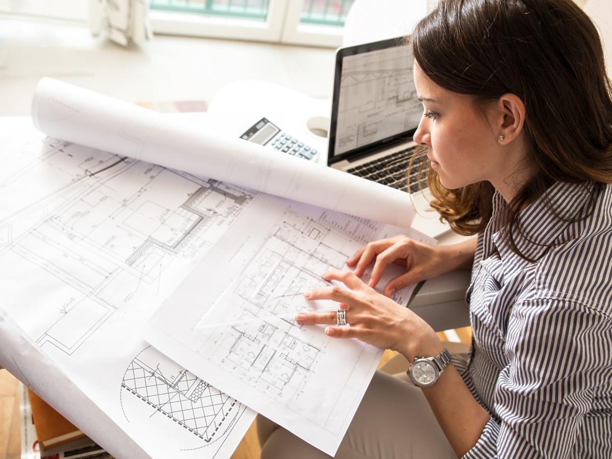 Kobieta pochyla się nad projektem architektonicznym