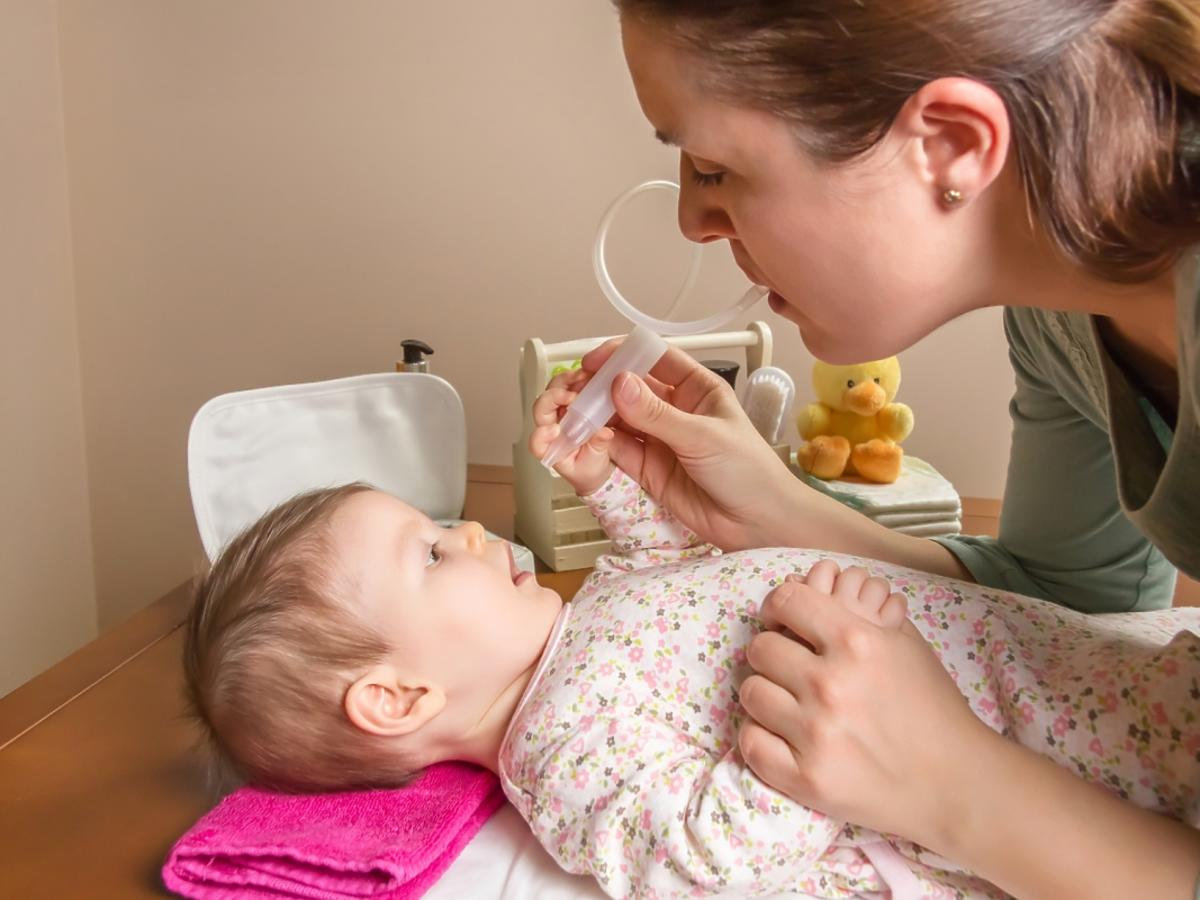 Kobieta podaje lekarstwo niemowlęciu